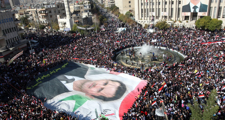 epa03017800 Syrian protesters display a giant portrait of President Bashar Assad during a pro-government rally at Sabe Bahrat square in downtown Damascus, Syria, 28 November 2011. According to media sources, thousands of supporters of Syrian President Bashar al-Assad rallied on 28 November across the country to protest the Arab League sanctions imposed on Damascus. Arab League foreign ministers endorsed on 27 November a package of economic sanctions against the Syrian government over its relentless clampdown against opposition. EPA/YOUSSEF BADAWI